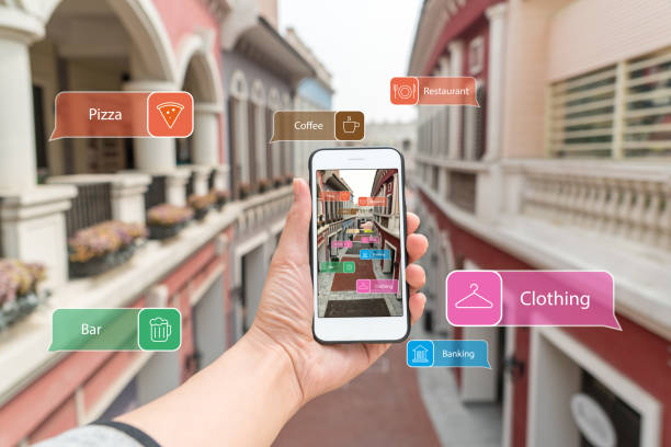 Cтоковое фото Augmented reality marketing street. Hand holding smart phone use AR application to check information