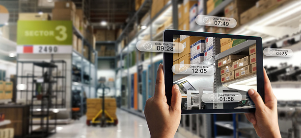 istock Augmented reality online shopping concept. E-commerce and digital marketing. Hand holding digital tablet smart phone use AR application to check order pick time on storage factory background. 1150204836