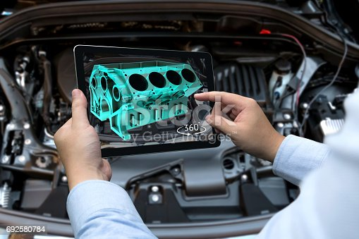 istock Augmented reality technology and engineering marketing concept. Hand holding tablet with AR service application to rotate 3d rendering of energy block 360 degrees with blur car engine room background 692580784