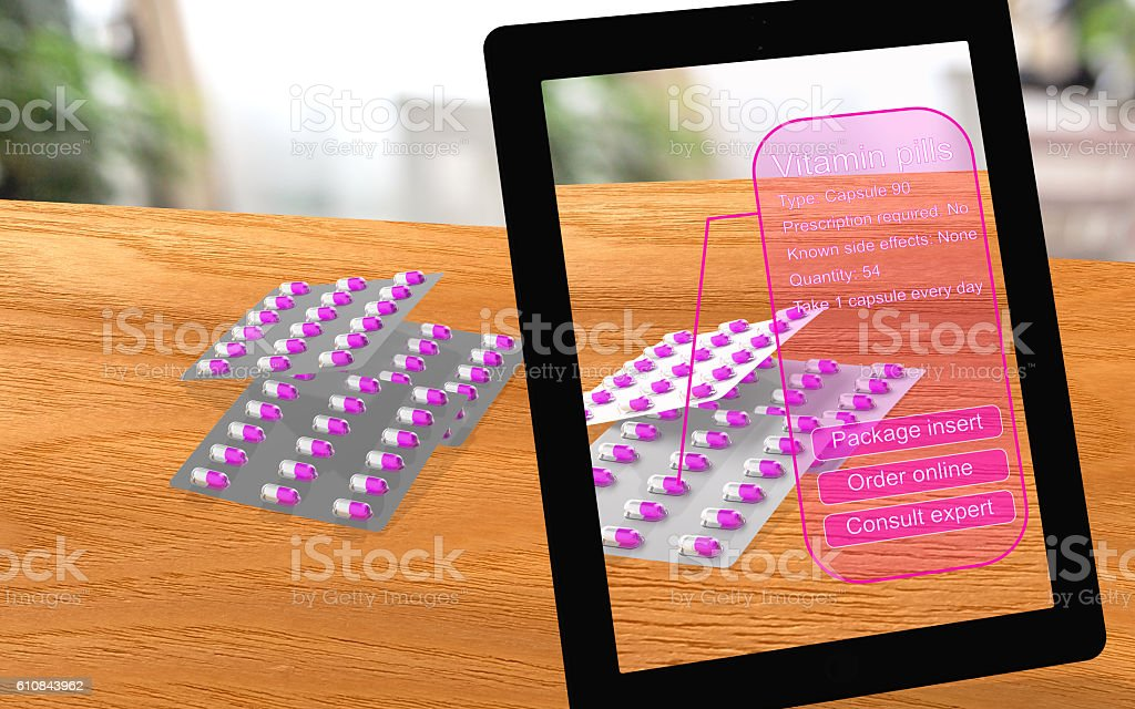 Augmented reality vitamin pills seen through a tablet stock photo