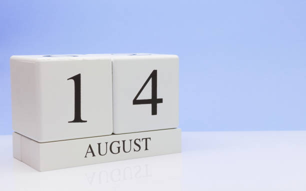 August 14st. Day 14 of month, daily calendar on white table with reflection, with light blue background. Summer time, empty space for text stock photo