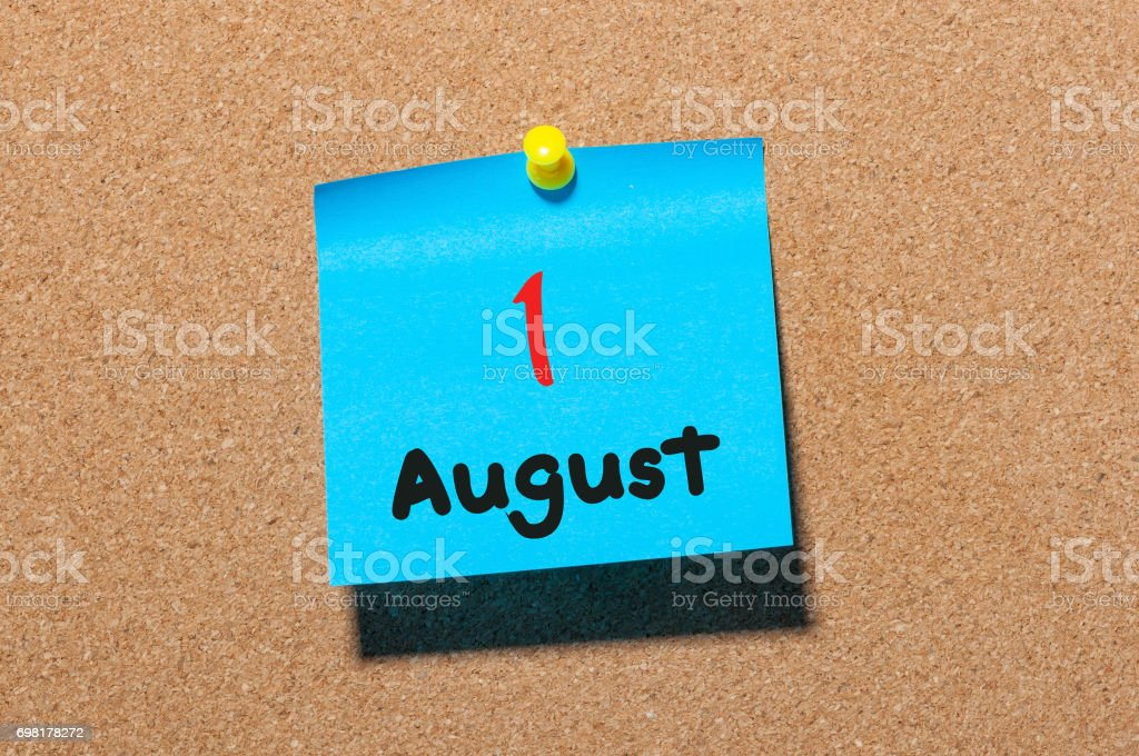 August 1st. Day 1 of month, color sticker calendar on notice board. Summer time. Close up stock photo
