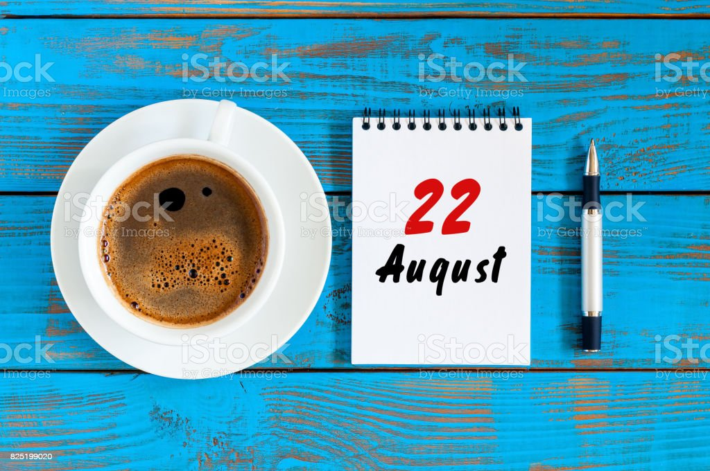 August 22nd. Day 22 of month, daily calendar on blue background with morning coffee cup. Summer time. Unique top view stock photo