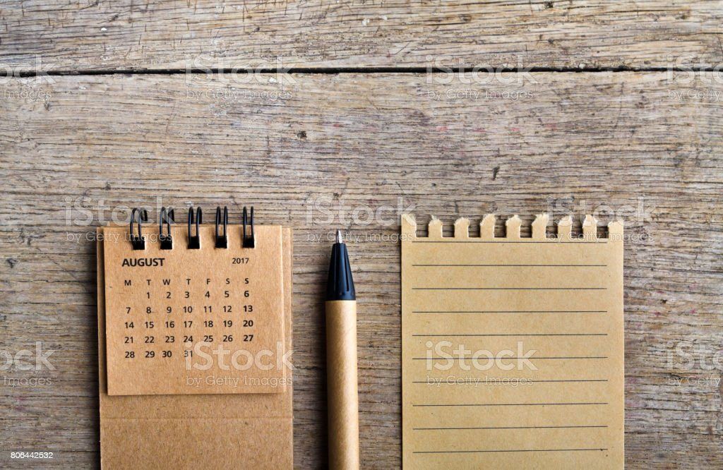 August. Calendar sheet. Two thousand seventeen year calendar, pen and list of paper on wooden background. - foto stock