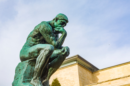 Paris, France - December 5, 2015: August Rodin's famous sculpture The Thinker in the grounds of the Musee Rodin, Paris