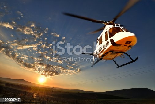A helicopter flying over vineyards lit by lat afternoon sun