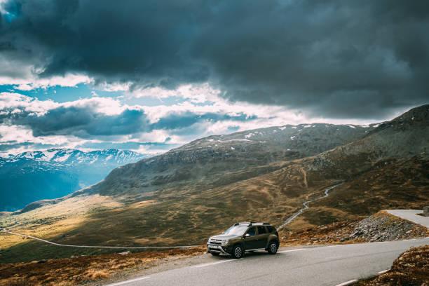 Aurlandsfjellet, Norway. Car Renault Duster SUV Parked Near Aurlandsfjellet Scenic Route Road In Summer Norwegian Landscape. Natural Norwegian Landmark And Popular Destination. stock photo