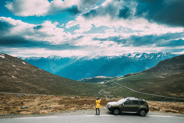 Aurlandsfjellet, Norway. Young Woman Tourist Traveler Photographer Taking Pictures Photos Near Parked Renault Duster Car. Aurlandsfjellet Scenic Route Road In Summer Norwegian Countryside Landscape stock photo