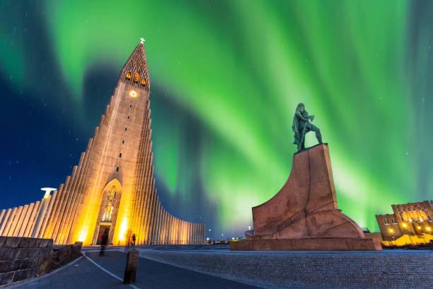 aurora borealis über hallgrimskirkja kirche im zentrum von stadt reykjavik in island - iceland stock-fotos und bilder