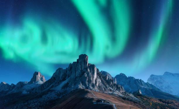 Aurora borealis über Bergen bei Nacht in Europa. Nordlicht. Himmel mit Sternen mit Polarlichtern und hohen Felsen. Schöne Landschaft mit Polarlichter, Gebäude auf dem Hügel, Bergrücken. reise – Foto