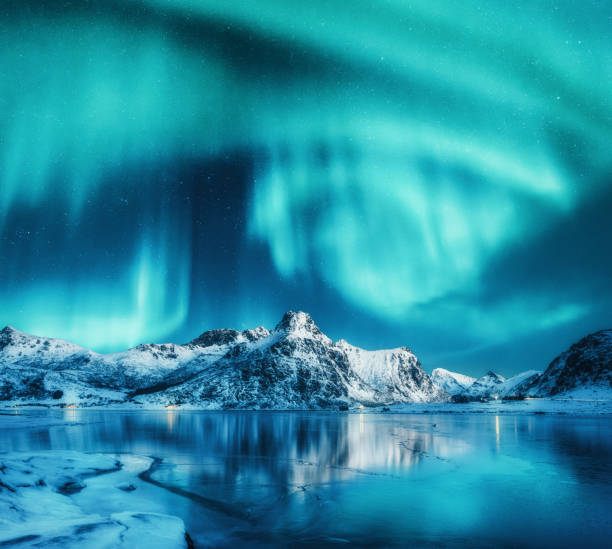 Aurora borealis above snowy mountains, frozen sea coast and reflection in water in Lofoten islands, Norway. Northern lights. Winter landscape with polar lights, ice in water. Sky with stars and aurora stock photo