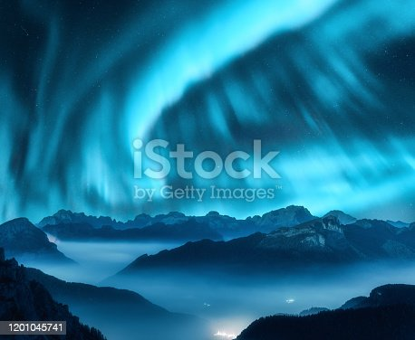 Aurora borealis above the mountains in fog at night. Northern lights. Sky with stars with polar lights and high rocks. Beautiful landscape with aurora, city lights in low clouds, mountain peaks. Space