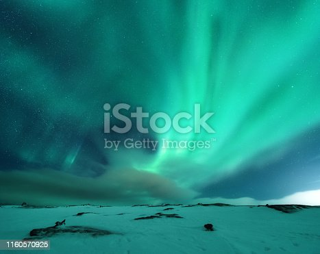 Aurora borealis above the snow covered mountain hill in europe. Beautiful Northern lights in winter. Night landscape with green polar lights and snowy mountains. Starry sky with aurora. Nature. Space