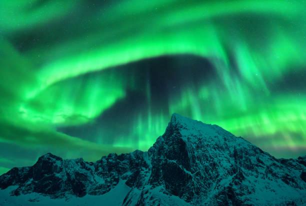Aurora borealis oberhalb des schneebedeckten Berges in den Lofoten-Inseln, Norwegen. Nordlichter im Winter. Nächtliche Landschaft mit Polarlichtern, schneebedeckte Felsen. Sternenhimmel mit Polarlichter. Hintergrund der Natur – Foto