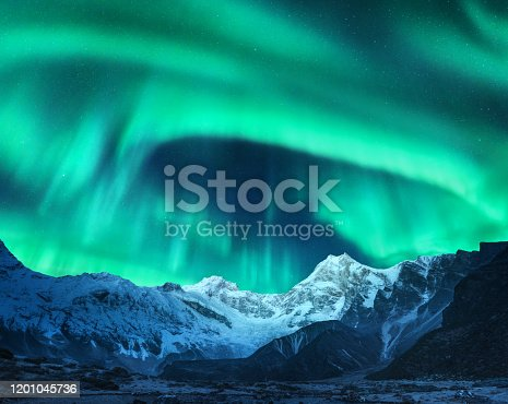 Aurora borealis above the snow covered mountain peak in Norway. Northern lights in winter. Night landscape with green polar lights and snowy mountains. Starry sky with aurora over the rocks. Space