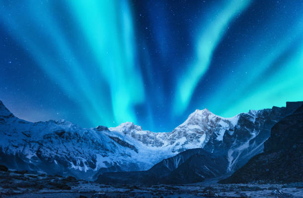aurora borealis above the snow covered mountain range in europe. northern lights in winter. night landscape with green polar lights and snowy mountains. starry sky with aurora over the rocks. space - den belitsky foto e immagini stock