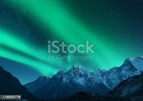 Aurora borealis above the snow covered mountain range in europe. Northern lights in winter. Night landscape with green polar lights and snowy mountains. Starry sky with aurora over the rocks. Space