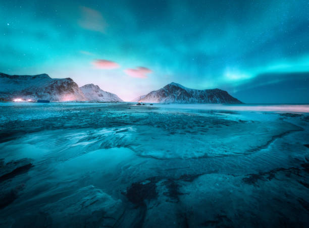Aurora borealis above the snowy mountain and sandy beach in winter. Northern lights in Lofoten islands, Norway. Starry sky with polar lights. Night landscape with aurora, frozen sea coast, city lights stock photo