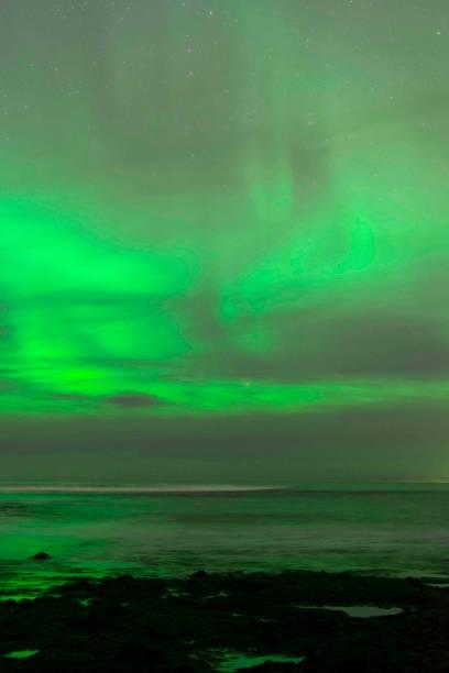 Aurora Borealis am Meer und Leuchtturm, Eiseland – Foto