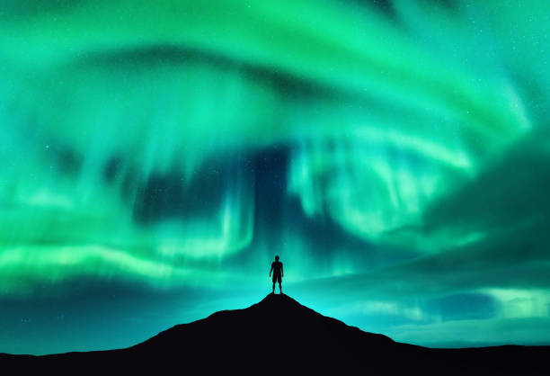 Aurora borealis and silhouette of a man on the mountain peak. Lofoten islands, Norway. Beautiful aurora and man. Alone traveler. Sky with stars and polar lights. Night landscape with northern lights stock photo
