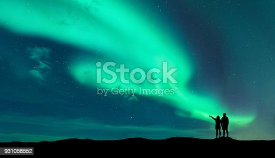istock Aurora borealis and silhouette of man and woman 931058552