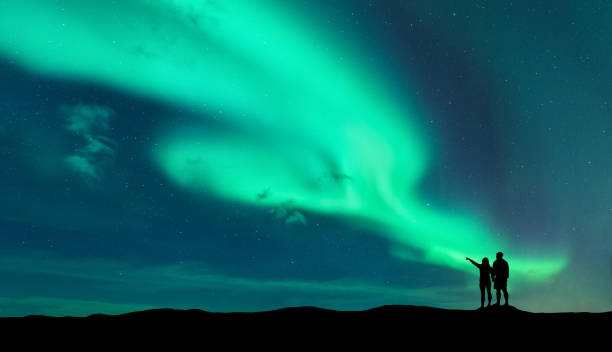 aurora borealis and silhouette of man and woman - aurora boreale foto e immagini stock