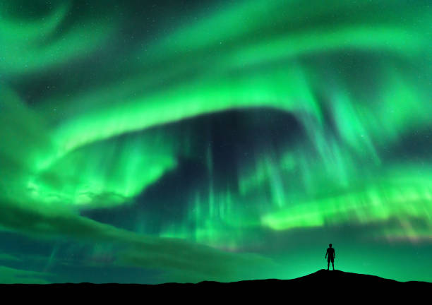 aurora borealis and silhouette of standing man. lofoten islands, norway. aurora and happy man. sky with stars and green polar lights. night landscape with aurora and people. concept. travel background - den belitsky foto e immagini stock