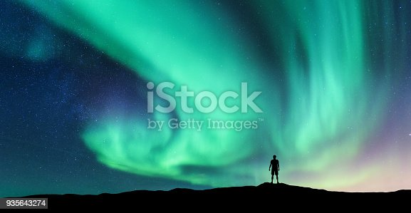 istock Aurora borealis and silhouette of standing man 935643274