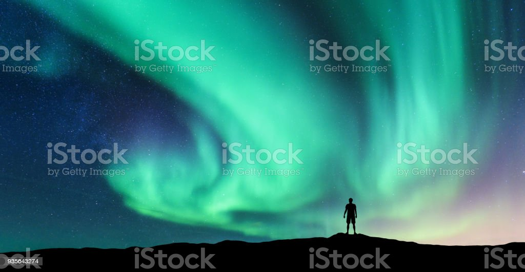 Aurora borealis and silhouette of standing man stock photo