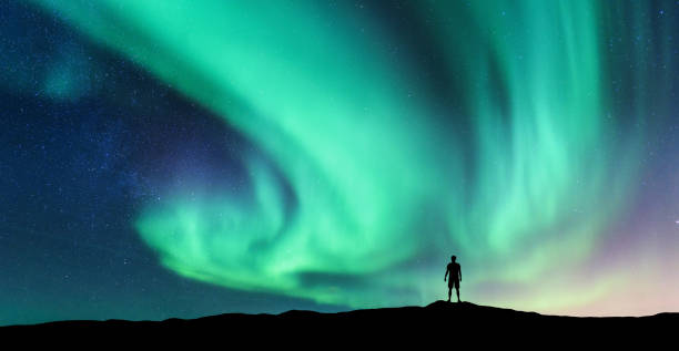 Aurora borealis and silhouette of standing man Aurora borealis and silhouette of standing man. Lofoten islands, Norway. Aurora and happy man. Sky with stars and green polar lights. Night landscape with aurora and people. Concept. Nature background lofoten stock pictures, royalty-free photos & images