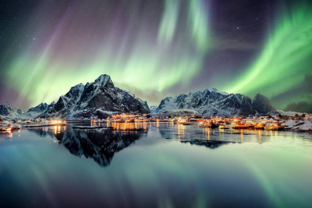 aurora borealis dancing on mountain in fishing village - aurora boreale foto e immagini stock