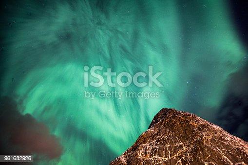 istock Aurora Borealis (Northern lights) dancing on steep mountain in sky 961682926
