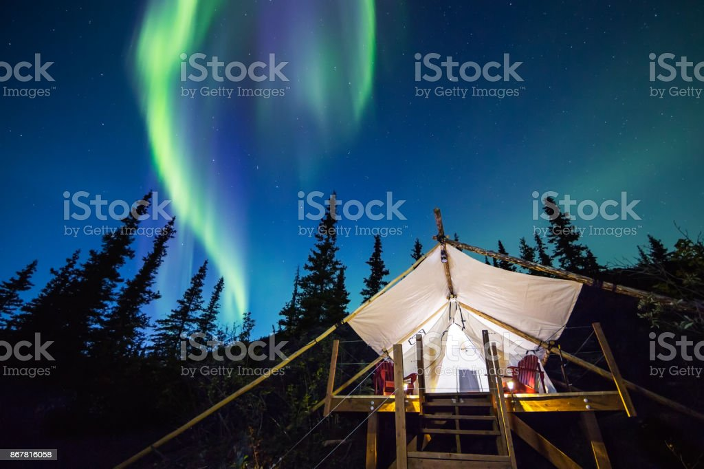 Aurora Borealis glowing green and pink over large canvas luxury camping tent in Alaska stock photo