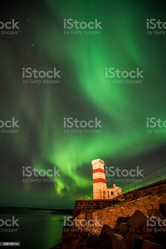 Aurora Borealis in a Winter sky over a lighthouse in Iceland stock photo