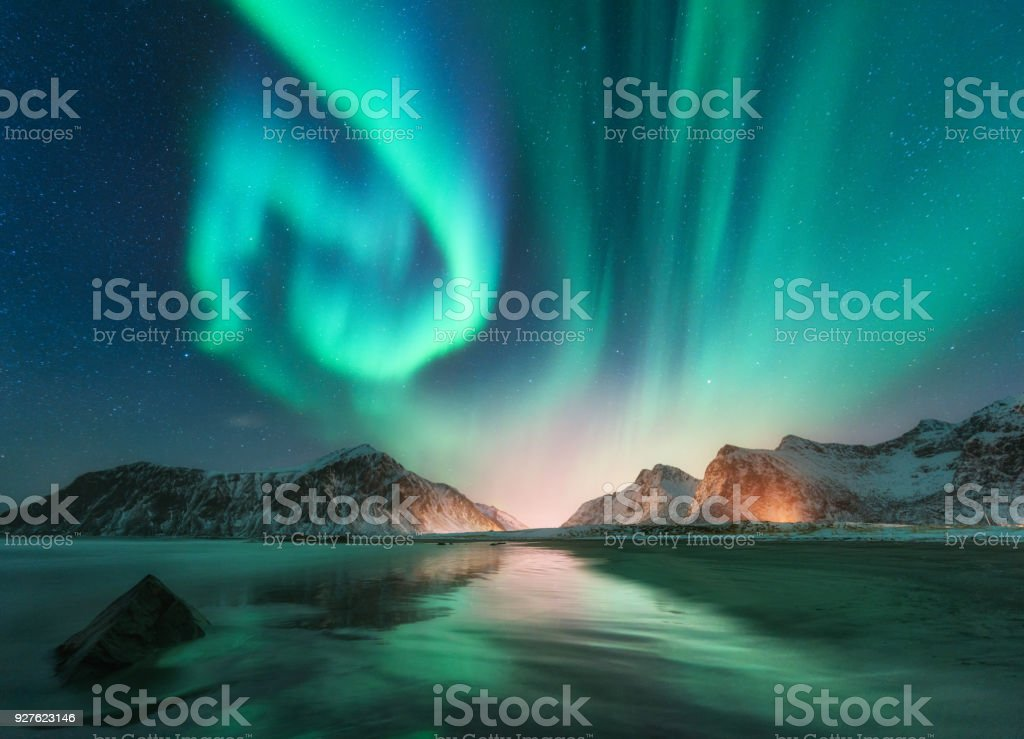 Aurora borealis in Lofoten islands, Norway. Aurora. Green northern lights. Starry sky with polar lights. Night winter landscape with aurora, sea with sky reflection, stones, beach and snowy mountains royalty-free stock photo