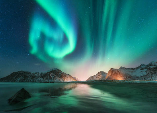 aurora borealis in lofoten islands, norway. aurora. green northern lights. starry sky with polar lights. night winter landscape with aurora, sea with sky reflection, stones, beach and snowy mountains - clima polar imagens e fotografias de stock