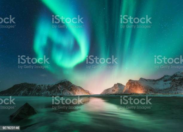 Photo of Aurora borealis in Lofoten islands, Norway. Aurora. Green northern lights. Starry sky with polar lights. Night winter landscape with aurora, sea with sky reflection, stones, beach and snowy mountains