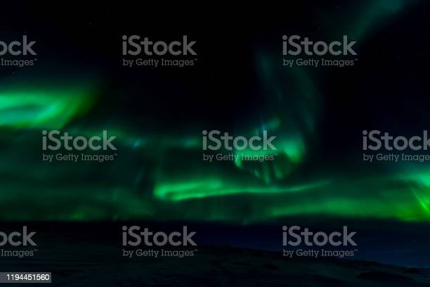 Photo of Aurora borealis in night northern sky. Ionization of air particles in the upper atmosphere.