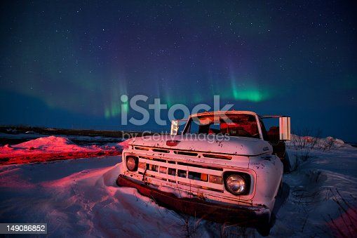 An old pick up truck stuck in the snow with the Aurora Borealis lighting up the sky above it.