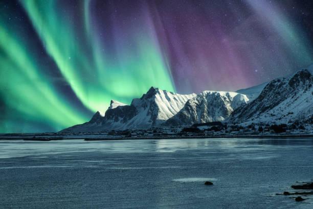 Aurora Borealis, Northern Lights Above of snowy mountain in Lofoten Islands stock photo