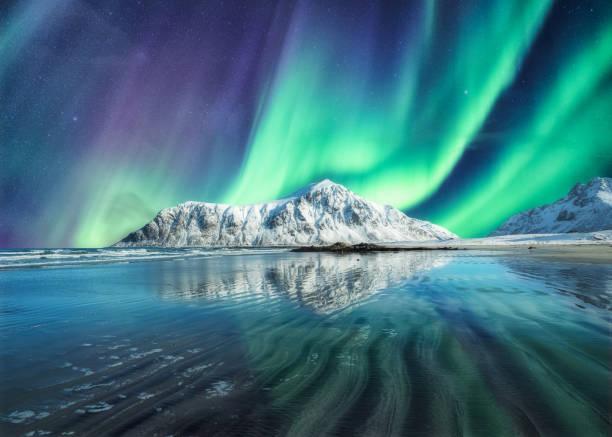 Aurora Borealis, Northern Lights Above on snowy mountain in Skagsanden Beach at Lofoten Islands stock photo