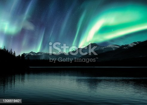 Aurora Borealis, Northern Lights over Canadian Rockies in forest on Pyramid lake at Jasper national park, Canada