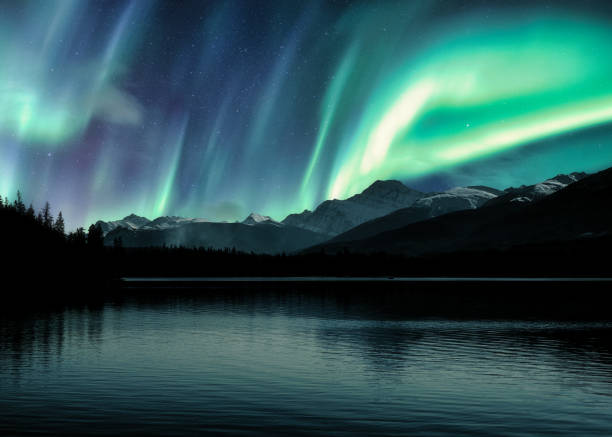 Aurora Borealis, Northern Lights over Canadian Rockies in forest on Pyramid lake at Jasper national park stock photo