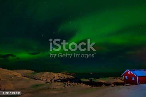 Northern lights (Aurora borealis) over the see and the snowy mountains of Lofoten islands, Norway.