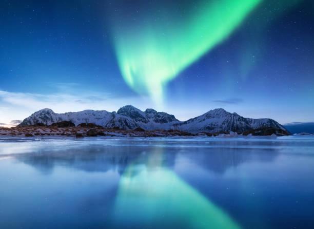 aurora borealis på ögruppen lofoten, norge. grönt norrsken. natthimlen med polart tänder. natt vinterlandskap med aurora och eftertanke på isen ytbehandlar. naturliga bakgrunden i norge - northern lights bildbanksfoton och bilder