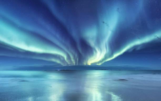 Aurora Boreal nas ilhas Lofoten, Noruega. Verde boreal acima do oceano. Céu noturno com luzes polares. Paisagem do inverno noite com aurora e reflexão na superfície da água. Fundo natural da Noruega - foto de acervo