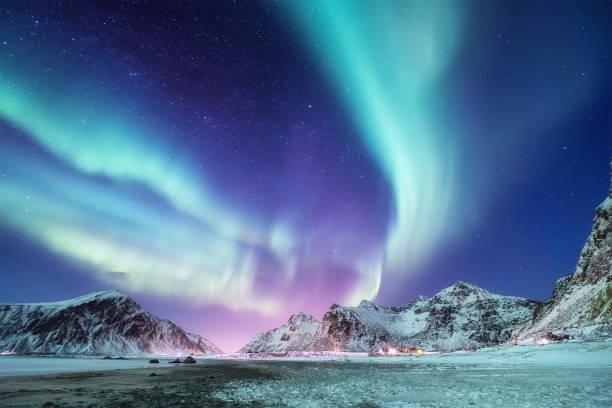 aurora borealis på lofotens öar, norge. grönt norrsken ovanför fjällen. natt vinterlandskap med aurora. naturlig bakgrund i norge - northern lights bildbanksfoton och bilder
