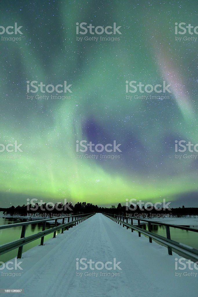 Aurora borealis over a bridge in winter, Finnish Lapland royalty-free stock photo