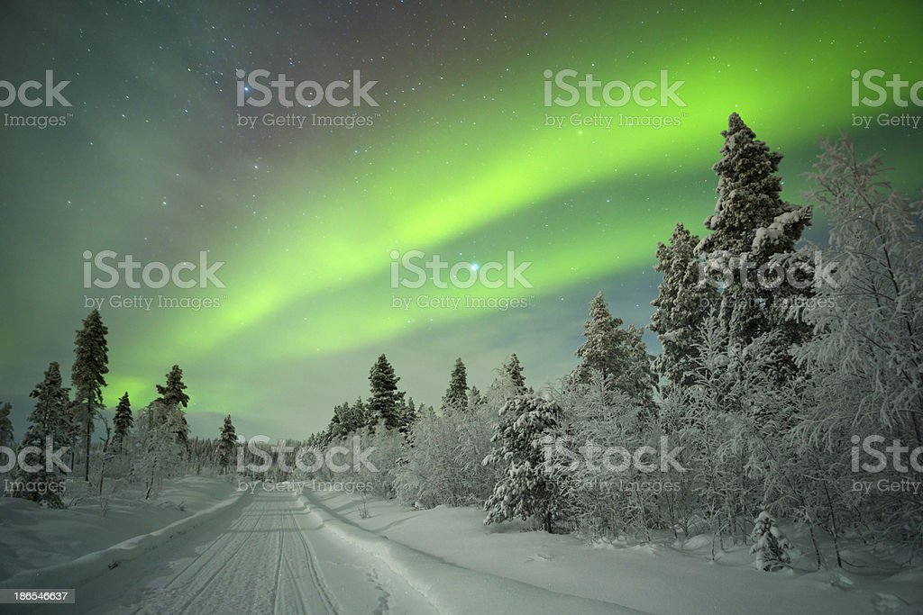 Aurora borealis over a track through winter landscape, Finnish Lapland stock photo