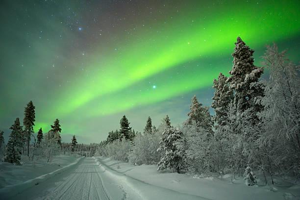 Aurora boreal más de una pista de invierno paisaje, laponia finlandesa - foto de stock